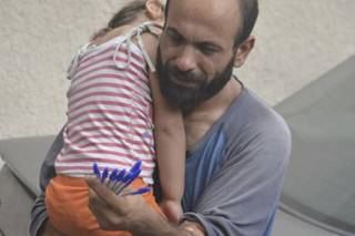 One Refugee Pictured Selling Biros Carrying His Child Is Set For New Life After Crowdfunding