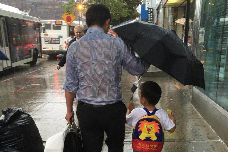 The Story Behind That Photo Of The Dad Sheltering His Son From The Rain UNILAD dad umbrella 22