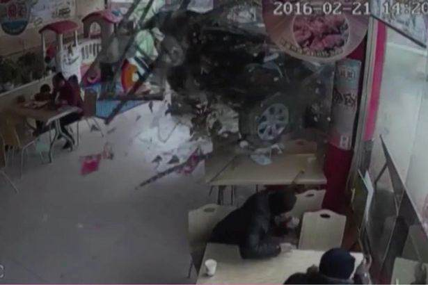 Car smashes through burger restaurant in China 1 Shocking Moment Car Crashes Through Restaurant And Traps Young Girl